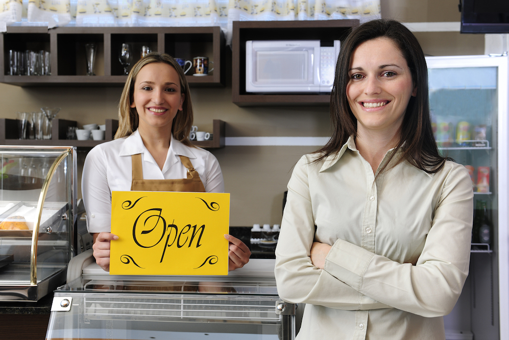 Photo of a business owner and a worker inside a cafe holding an open sign -- business insurance in Detroit STATE | Mason-McBride