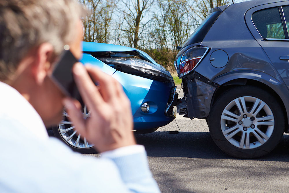 Photo of a two-car collision and a man using a cell phone -- auto insurance in Detroit MI | Mason-McBride