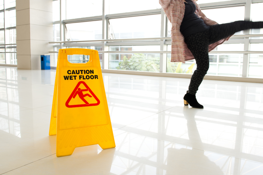Photo of a person sliding on a wet floor in an office building and wet floor sign nearby -- general liability in Detroit MI | Mason-McBride