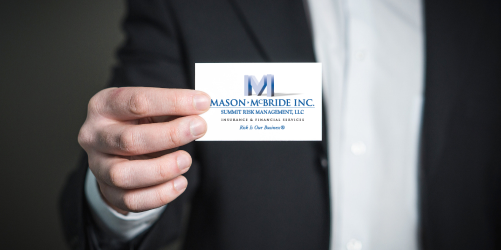 Photo of a man in a suit coat holding a card with the Mason-McBride logo --Rate Mason McBride Insurance Agency