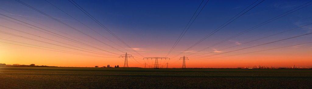 Photo of sunset and electrical power lines in the distance