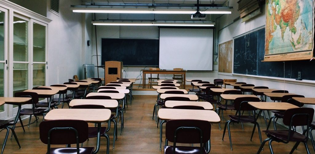 Photo of the inside of an empty classroom with desks and maps -- Education industry insurance