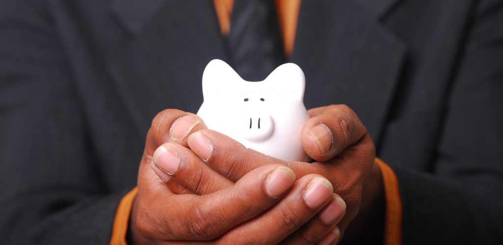 Photo of a man in a suit and tie holding a small piggy bank in his hands -- Financial Services Industry Insurance