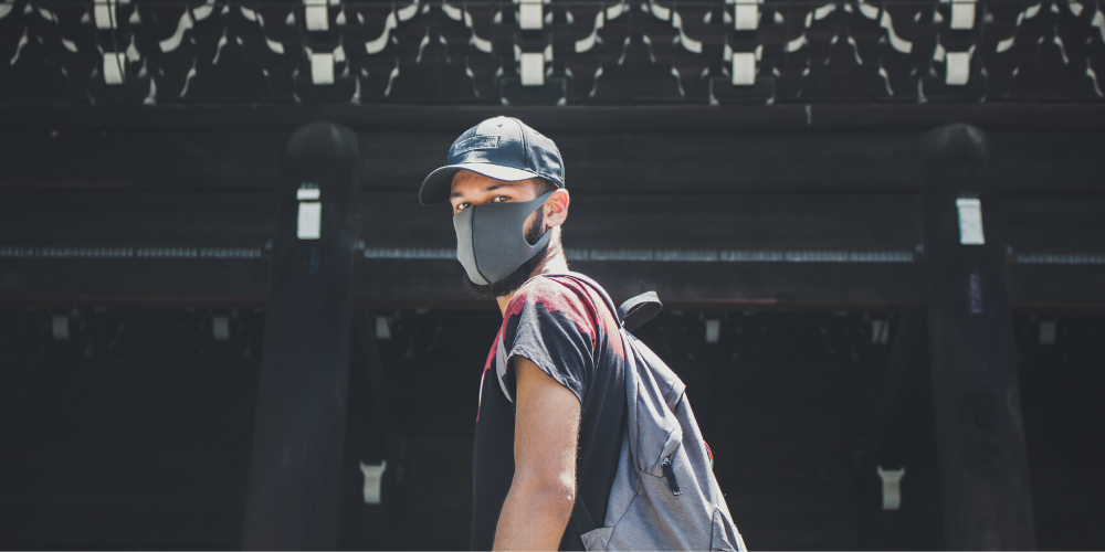 Photo of a man wear a face mask and carrying a backpack