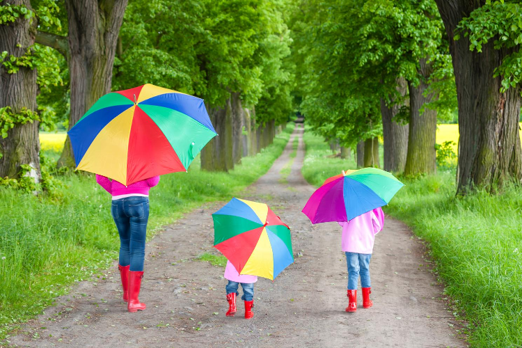 Photo of a woman with children, each carrying umbrellas on a country road.