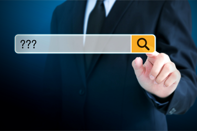 Photo of man in a suit inputting question mark symbol in a search bar