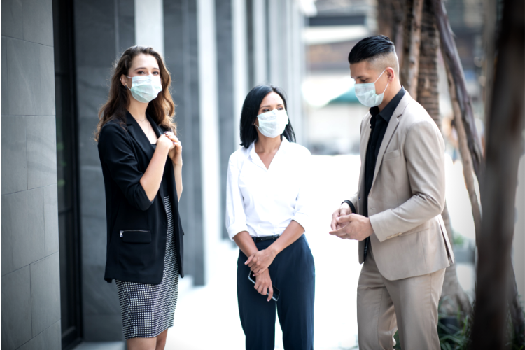 three working professionals gathered outside on sidewalk wearing masks