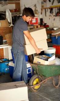 Photo of a young man moving boxes in a home garage.
