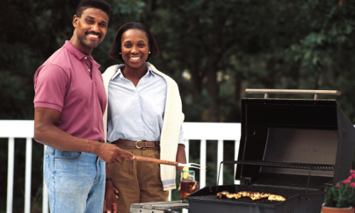 Photo of a young couple on a deck using a barbeque grill.