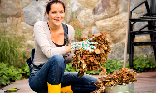 Photo of a woman cleaning up leaves outdoors.